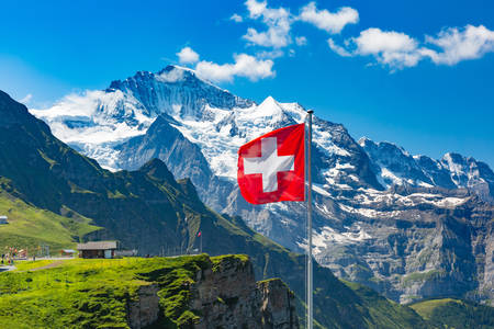 Swiss flag on the background of the Jungfrau mountain