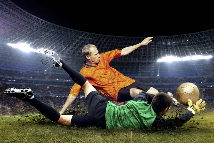 Football player and goalkeeper jump