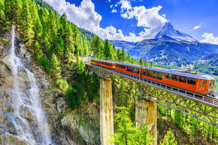 Panoramic train in the mountains with a waterfall