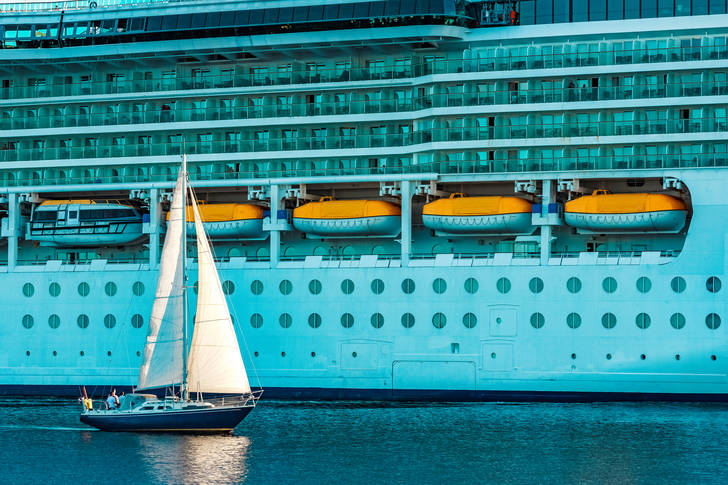 Sailboat with cruise liner
