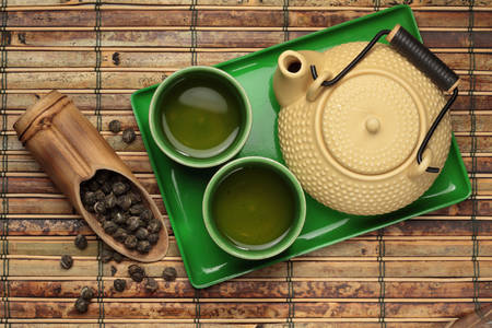 Teapot and cups with green tea