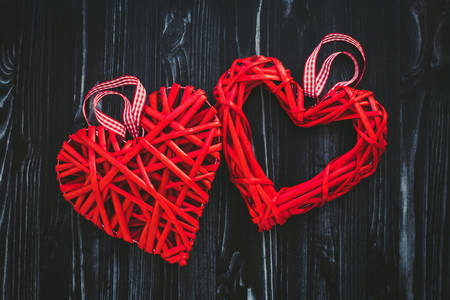 Red wicker hearts on dark wooden background