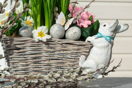 Easter bunny on a basket with flowers