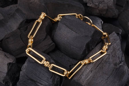 Gold bracelet on black coal